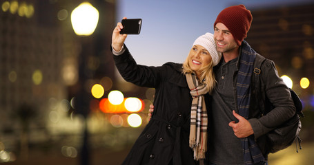 Happy white couple taking a selfie outdoors at night in the city