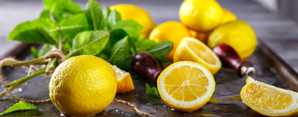 Lemons fresh.Citrus on metallic Background with green mint and pieces of ice.Mojito.selective focus.