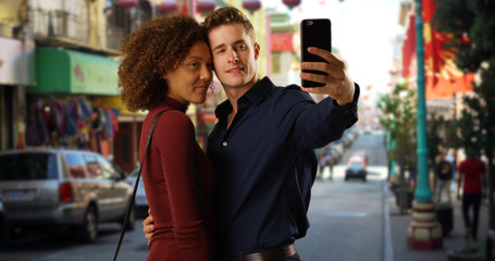 Happy mixed race couple using smartphone to take selfie in Chinatown