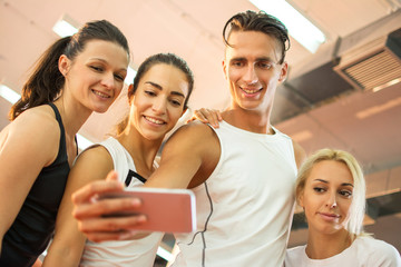 Group of young people taking a selfie photo in a gym.
