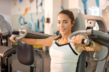 Young woman exercising on machine at gym.