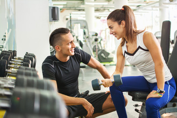 Personal trainer working with his client in gym. Male personal trainer talking with young fitness woman while she lifting weights.
