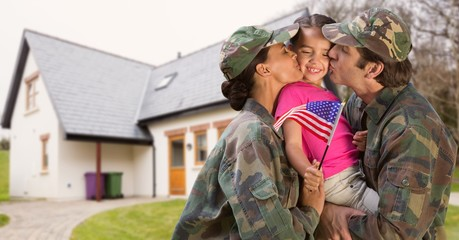 Happy parents in soldiers uniform kissing their daughter