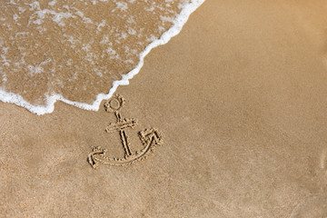 Anchor drawn on the beach sand. Summer holidays background