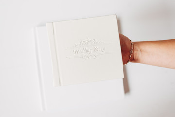 White classic wedding book in white background. Female hand holding a book