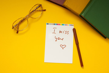 """The inscription """"I miss you"""" on a yellow background, glasses and"""