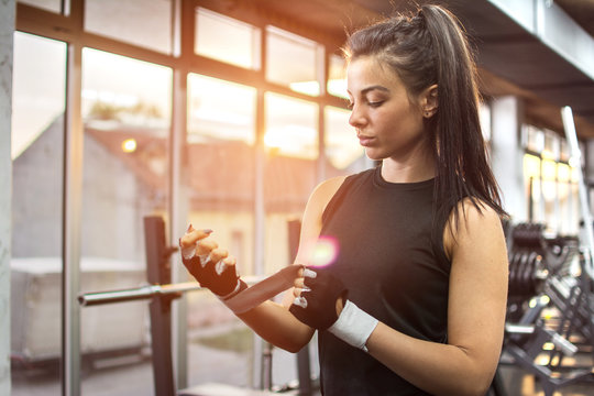Young fitness lady putting on a sport gloves in gym.