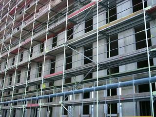 Baugerüst an der Fassade einen Rohbaus aus grauem Beton am Mittelhafen von Münster in Westfalen im Münsterland