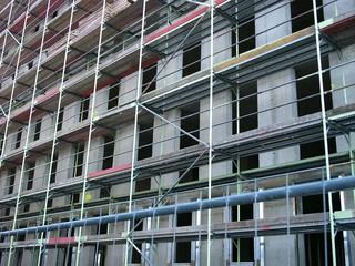 Baugerüst aus Stahlrohr vor einer grauen Fassade aus Beton mit Fensteröffnungen am Mittelhafen von Münster in Westfalen im Münsterland