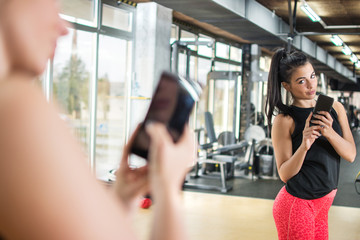 Young sportswoman with smartphone taking mirror selfie in gym.
