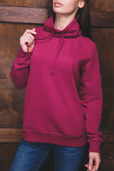 Young woman wearing blank magenta sweatshirt with area for your logo or design, mock-up of template magenta sweatshirt, wooden wall in the background