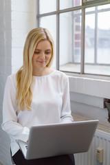 junge blonde frau mit laptop