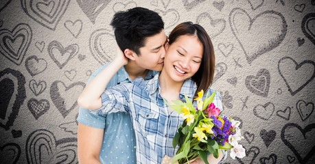 Man kissing woman while holding bouquet