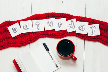 "Coffee in red cup, notebook with pen and word ""saturday"" on the red scarf. On white wooden table"