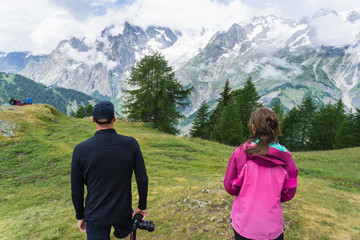 Two hikers, a man and a woman, look out over the snow covered mountains and deep forest valleys during a hike near Courmayeur, Italy
