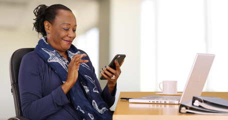 An African American businesswoman uses her mobile phone at her desk