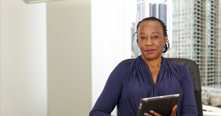 An African American businesswoman holding a tablet in her Chicago office