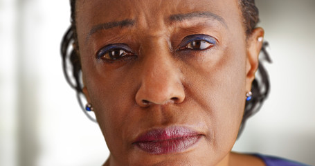 A close-up of a elderly black woman looking sad