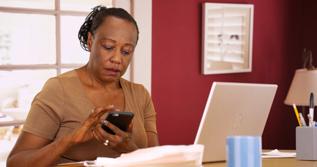 An older black woman uses her phone and laptop to do her taxes