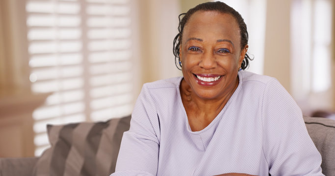 An older black woman happily looks at the camera