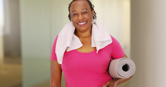 An elderly African American woman poses for a portrait after her workout