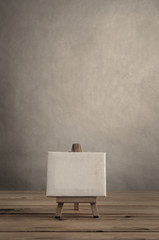 Blank Art Canvas on Wooden Easel against Empty Wall with Planked