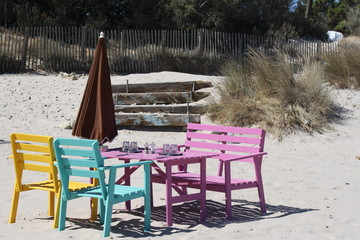Corsica, Calvi, colorful tables and benches at beach