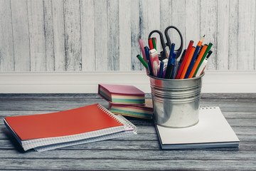 colored pencils and scissors in a glass, red notepad on a table