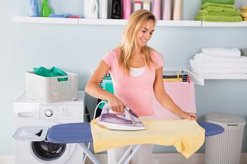 Smiling Woman Ironing T-shirt On Ironing Board
