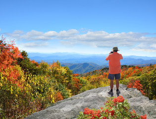 Man standing on top of the mountain taking photos ,looking at beautiful autumn mountains landscape foliage. Blue Ridge Mountains. Copy space. North Carolina, USA.