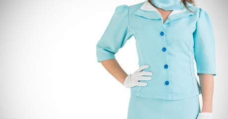 Air hostess in uniform standing with hand on hip