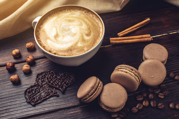 Coffee with macarons and chocolate in the shape of heart.