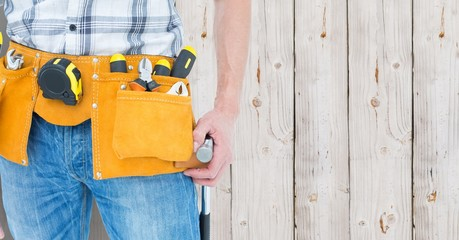 Mid section of handyman with tool belt around his waist