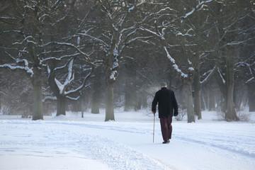 Einsamer alter Mann läuft am Gehstock durch den Winter