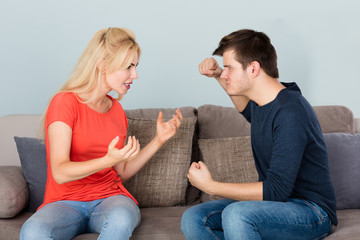 Couple Sitting On Couch Quarreling With Each Other