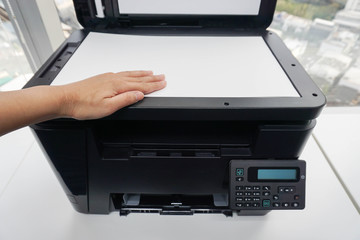 woman place A4 paper sheet on printer for scanning