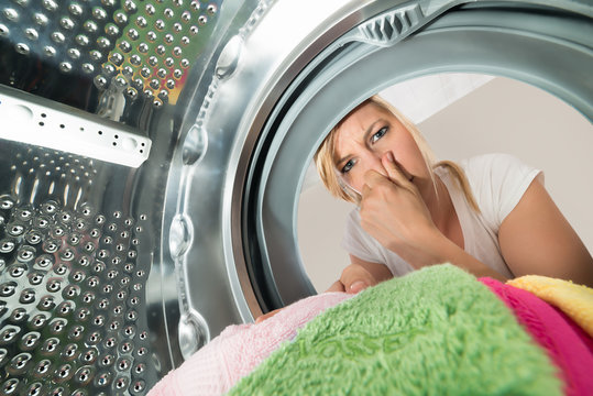 Woman Inserting Stinking Clothes In Washing Machine