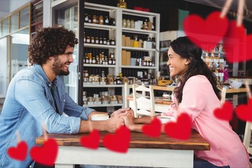 Composite image of romantic couple holding hands in a restaurant