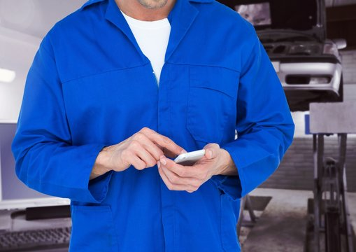Mid section of car mechanic using mobile phone