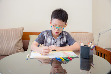 Young Asian boy at the table draw with color pencils