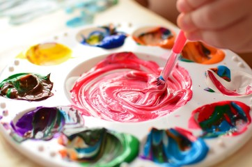 Child mixing paint on a palette of colorful paint