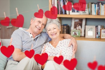 Composite image of red heart and senior couple embracing on sofa