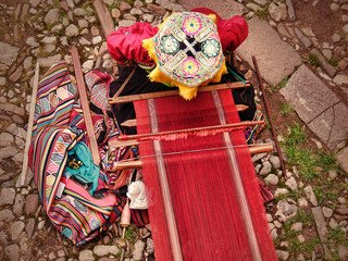 Top view of peruvian woman in traditional clothes which weaves  handmade carpet