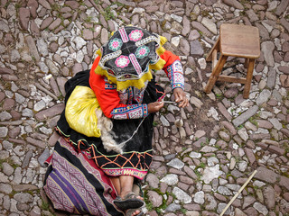 Top view of peruvian woman in traditional ethnic dress which is spinning alpaca wool