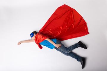 Superhero kid flying in superman costume