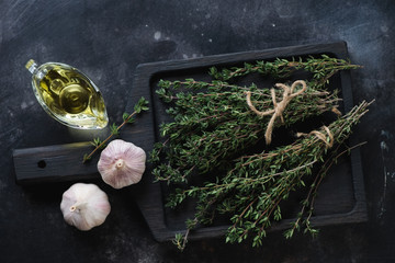 Dark wooden serving board with fresh thyme, garlic and olive oil