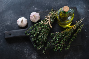 Bunches of fresh thyme, bottle of olive oil and garlic bulbs
