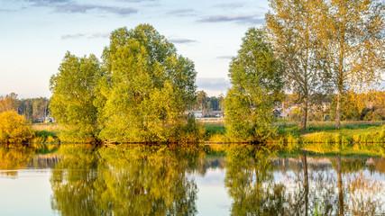 летний пейзаж на берегу реки с отражением деревьев в воде, Россия, Урал,