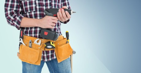 Mid section of handy man with tool belt holding a drill