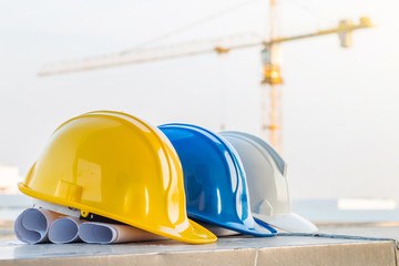 The safety helmet and the blueprint at construction site with cr